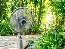 The  electric table fan in the garden Royalty Free Stock Photography