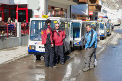 Electric taxi drivers talk at the parking lot in Zermatt, Switzerland. Royalty Free Stock Image