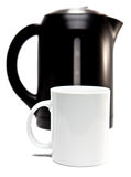 Electric tea kettle on a white background and a mug.Focus on a tea mug Stock Photos