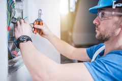 Electric Technician Job. Caucasian Professional Electrician in His 30s Finishing Electric Box Inside the Apartment Stock Photography