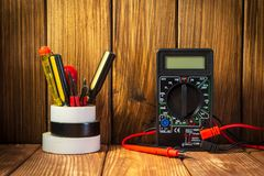 Electric tester and electronics tool kit on wooden background. Electrical tester and a set of tools for electronics repair on vintage wooden background royalty free stock photos