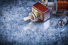 Electric toggle switch transformer lamp-holder on scratched meta Royalty Free Stock Photo