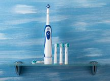 Electric toothbrush with colored tips on the glass shelf. In the bathroom stock photo