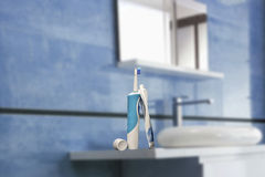 Electric toothbrush with toothpaste. In a blue bathroom Royalty Free Stock Images
