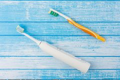 Electric Toothbrush Versus Normal Manual Brush Concept On High C. Ontrast Blue And White Wood Background Top Angle royalty free stock images
