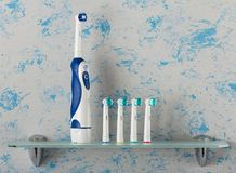 Free Electric Toothbrush With Extra Nozzles Of Different Colors On Glass Shelf Stock Photo - 109185010