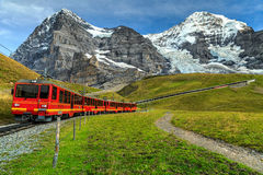 Electric tourist train and Eiger North face,Bernese Oberland,Switzerland. Famous electric red tourist train coming down from the Jungfraujoch station(top of Stock Image