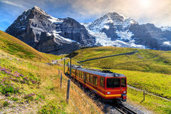 Electric tourist train and Eiger North face,Bernese Oberland,Switzerland. Famous electric red tourist train coming down from the Jungfraujoch station(top of Stock Photography