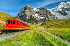Electric tourist train and Eiger North face, Bernese Oberland, Switzerland. Famous electric retro red tourist train coming down from the Jungfraujoch stationtop Royalty Free Stock Images