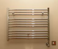 Bathroom towel radiator. An electric towel radiator in a bathroom  with a switch and fuse on the cream painted wall beside it Royalty Free Stock Photography