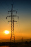 Electric tower at sunset with sun Stock Photography