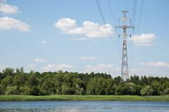 Electric tower among trees. High voltage electric pylon near water. Interaction of nature and industry royalty free stock photos