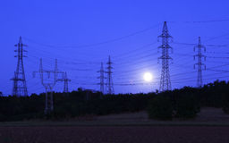 Electric towers at moonlight Stock Image