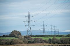 Electric towers over green fields in Lancashire, UK. royalty free stock image