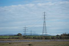 Electric towers over green fields and a river stock photo