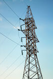 Electric towers with wires. Electric high voltage tower with electric line against clear blue sky Stock Photos