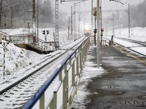 Electric Train Arriving. Electric railway and a train arriving, winter scene, station platform in the foreground Royalty Free Stock Photo
