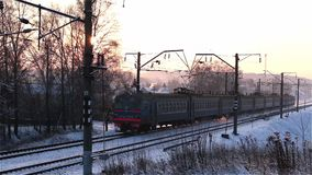 Electric train moving from right to left at winter sunset. Blue russia belarus stock video footage