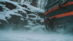 Electric train riding on railroad pathway in canyon covered in snow. Green electric train riding on railroad pathway in canyon covered in snow, cold cloudy stock video