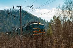 Electric train RZHD on mountain forest background in springtime royalty free stock image