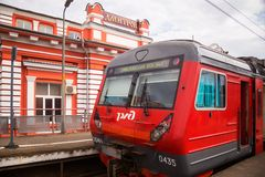Electric train stands at platform against station in the city of Stock Image