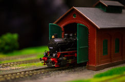 Electric train toy, rail transport modelling. Black locomotive serial number 89008 departs from a red brick depot with green gates royalty free stock image