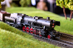 Electric train toy, rail transport modelling. Black locomotive serial number 555 with red wheels and a star on a background of green grass stock photography