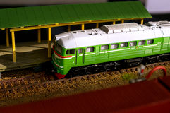 Electric train toy, rail transport modelling. Green locomotive at the station stock image