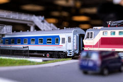 Electric train toy, rail transport modelling. Railroad crossing with a moving locomotive SS7s and car on background of the bridge royalty free stock image