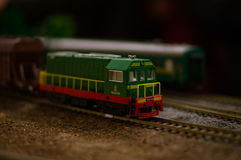 Electric train toy, rail transport modelling. Soviet green diesel locomotive ChMe2-024 with a red stripe and yellow fence stock image