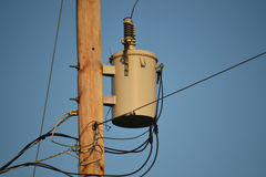 Electric transformer on pole. An electric transformer on light pole with blue sky background Stock Photo