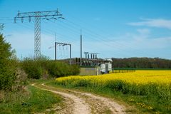 Electric transformer station stands on a canola field royalty free stock photos