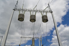 Electric transformers against clouds Stock Photo