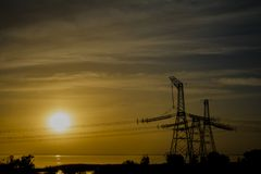 Electric transmission line on a colorful sunset royalty free stock photos