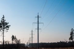 Electric transmission lines in winter,snow-covered fields in the evening stock image