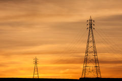 Electric Transmission Towers in orange sunset. Stock Photos