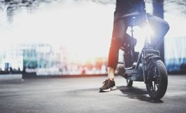 Electric urban transportation.Young man ready to ride his electric scooter bike in the center of a city. Electric urban transportation.Young man ready to ride royalty free stock photo
