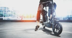 Electric urban transportation.Young man ready to ride his electric scooter bike in the center of a city. Wide.  royalty free stock image