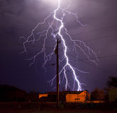Electric Utility Lightning. Extremely detailed lightning bolt behind electric utility pole Stock Photo