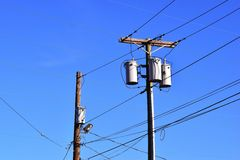 Electric utility poles. With  transformers against blue sky background Stock Image