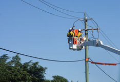 Electric utility workers. Two utility repairmen linesmen working on power lines from a bucket truck Royalty Free Stock Photos