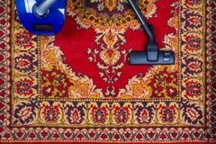Electric vacuum cleaner on the background of an old carpet, top view. Of flat lay royalty free stock photo