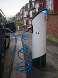 An electric vehicle being charged at a charging station at a residential street in London, UK. In the evening stock photo