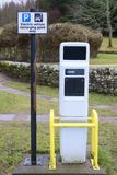 Electric vehicle car recharging point sign and charging station to plug in parking space in park. Loch Lomond Scotland for tourists and travellers camp life Royalty Free Stock Photos