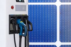 Electric vehicle charging Ev station and plug of power cable supply for Ev car on solar cells or photovoltaic panel background.  stock photography
