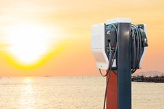Electric vehicle charging Ev station with plug of power cable supply for Ev car  on sun rise background.  stock image