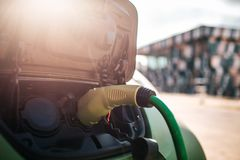 Electric vehicle charging station. Charging an electric car with the power cable supply plugged in. Eco-friendly car for royalty free stock image