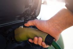 Electric vehicle charging station. Close-up of hand charging an electric car with the power cable supply plugged in. Eco stock image
