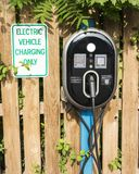 Electric Vehicle Charging Station at a hotel. An electric vehicle charging station is in the parking lot of a hotel for guest to use for freel Royalty Free Stock Photos