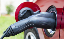 Electric vehicle plugged in Royalty Free Stock Photos